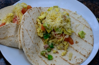 Layer some of the egg, fresh tomato, avocado, and cheese onto one of the tortillas then squeeze some lime over it. (hint leave some space at the bottom to fold it)